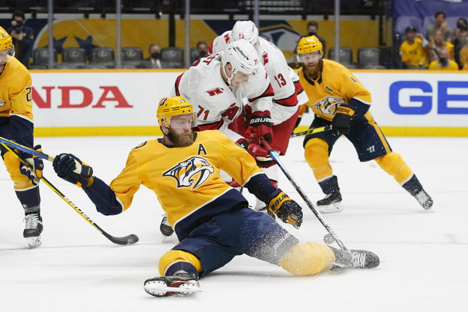 Nashville Predators defenseman Mattias Ekholm, front, falls as he chases the puck with Carolina Hurricanes right wing Jesper Fast (71) during the first period in Game 3 of an NHL hockey Stanley Cup first-round playoff series Friday, May 21, 2021, in Nashville, Tenn. (AP Photo/Mark Humphrey)