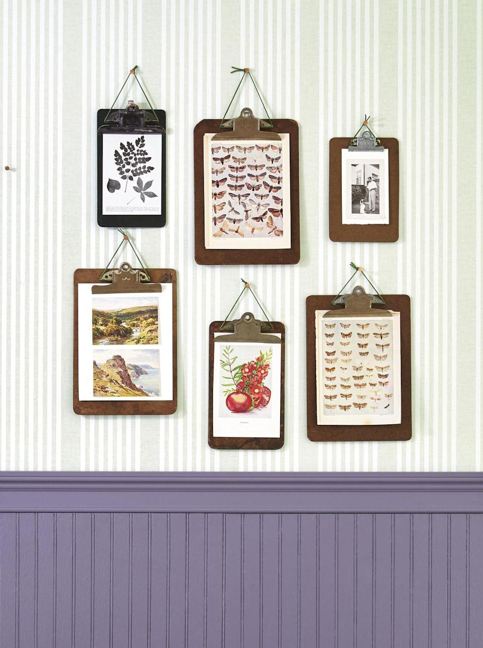 <p>Gallery walls add instant decor to an unadorned wall but frames can get quite expensive. For this budget-friendly arrangement, simply clip prints to vintage clipboards. Thread a piece of leather jewelry cord under the clip, knot it at the top, and hang with a pushpin. Bonus: You can easily change out the images every season. </p>