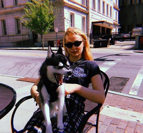 Sophie Turner sitting outside with a dog on her lap