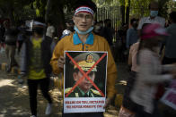 A Chin refugee from Myanmar holds a portrait of Commander in chief, Senior Gen. Min Aung Hlaing during a protest against military coup in Myanmar, in New Delhi, India, Wednesday, March 3, 2021. (AP Photo/Altaf Qadri)