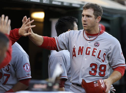 Los Angeles Angels' J.B. Shuck, right, is congratulated after scoring against the Oakland Athletics in the third inning of a baseball game on Thursday, July 25, 2013, in Oakland, Calif. Shuck scored on a single by Angels' Albert Pujols. (AP Photo/Ben Margot)