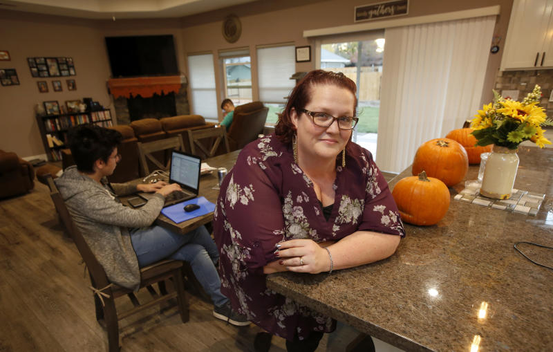 Victoria Sinclaire is seen in her recently rebuilt home with her two exchange students in Paradise, Calif., Tuesday, Nov. 5, 2019. It took Sinclaire six hours to escape the flames from last year's wildfire that destroyed 90 percent of Paradise. Sinclair's is one of just nine homes that have been rebuilt, but the town is on track to issue 500 building permits by year's end. (AP Photo/Rich Pedroncelli)