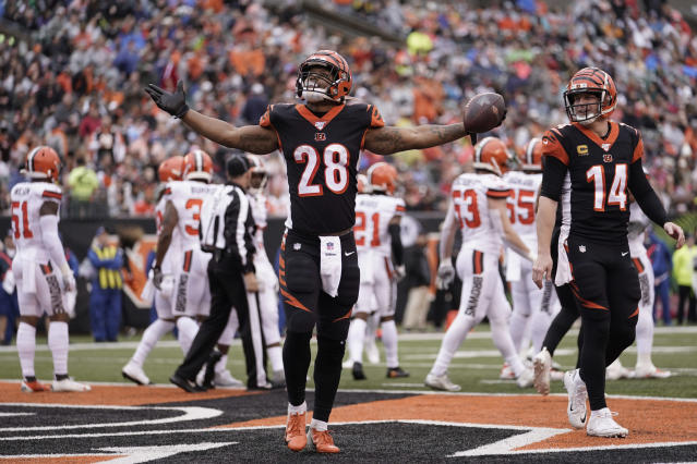Cincinnati Bengals running back Joe Mixon (28) celebrates after a 3-yard touchdown during the first half of an NFL football game against the Cleveland Browns, Sunday, Dec. 29, 2019, in Cincinnati. Quarterback Andy Dalton (14) smiles as he looks on. (AP Photo/Bryan Woolston)