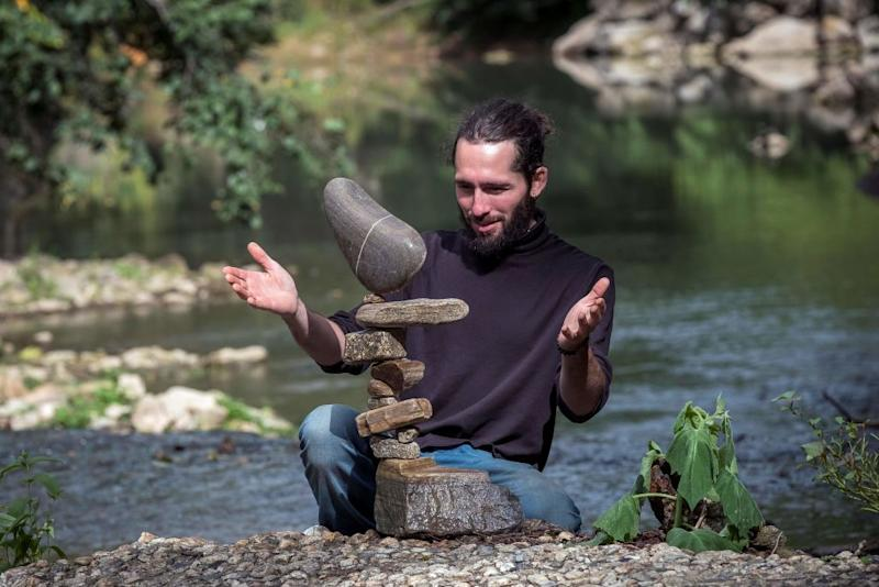 French artist and rock balancer SP Ranza looks at his temporary sculpture made of stones collected in the river on October 10, 2019 near Mazamet, southern France. - SP Ranza won the Stone Stacking European Championships in Dunbar, Scotland, last April 2019 and will take part in the llano Earth Art Festival and World Stone Balancing competition 2020.