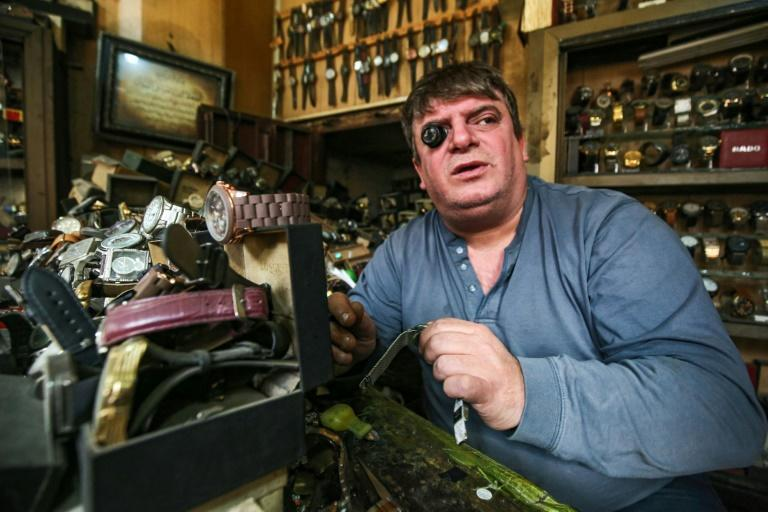 Watch repairman Youssef Abdelkarim sits wearing a jewellery magnifier as he fixes a timepiece at his workshop on Rasheed Street in Iraq's capital Baghdad