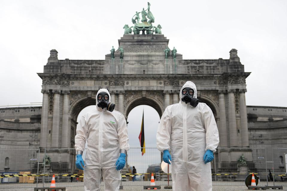 Belgian military personnel members wearing full protective suits stand in front of the Cinquantenaire arch during the disinfection of an ambulance amid the coronavirus disease (COVID-19) outbreak in Brussels, Belgium November 13, 2020. REUTERS/Johanna Geron
