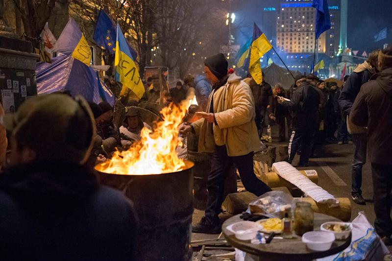 Pro-European Union activists warm themselves near bonfires during a rally in the Independence Square in Kiev, Ukraine, Friday, Dec. 13, 2013. Ukraine's president proposed an amnesty Friday for all protesters facing criminal charges in the country's wave of massive anti-government demonstrations. President Viktor Yanukovych made the offer at a round-table meeting that included three leaders of the opposition that has orchestrated more than three weeks of anti-government protests, flooding the streets of Kiev with hundreds of thousands of people. (AP Photo/Alexander Zemlianichenko)