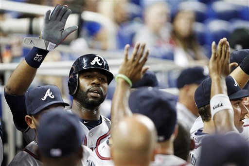 Atlanta Braves' Jason Heyward, rear left, is congratulated by teammates after scoring on a single by Martin Prado during the first inning of a baseball game against the Miami Marlins, Monday, Sept. 17, 2012, in Miami. (AP Photo/Wilfredo Lee)