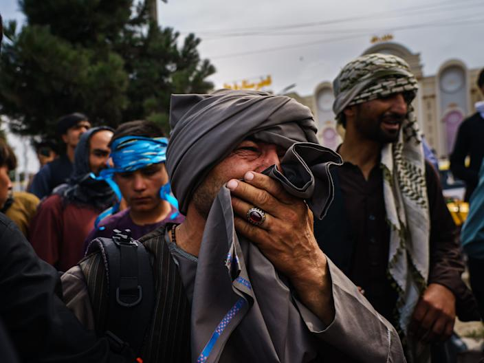 A man cries as he watches fellow Afghans get wounded by Taliban fighters