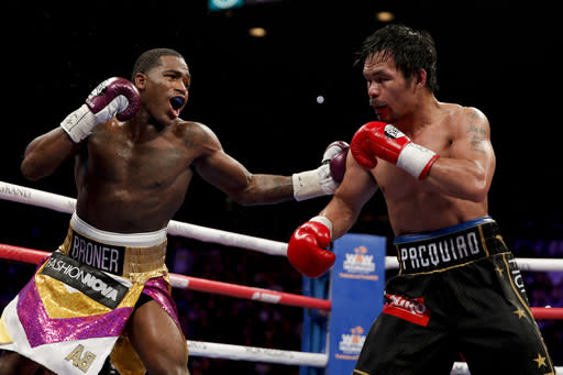 Adrien Broner, left, hits Manny Pacquiao during the WBA welterweight title boxing match Saturday, Jan. 19, 2019, in Las Vegas. (AP Photo/John Locher)
