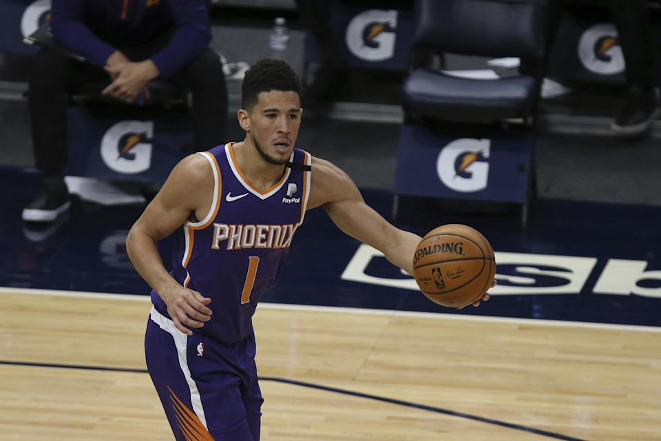 Phoenix Suns' Devin Booker (1) handles the ball in the first half of an NBA basketball game against the Minnesota Timberwolves, Sunday, Feb. 28, 2021, in Minneapolis. (AP Photo/Stacy Bengs)