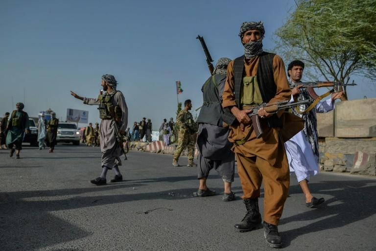 Afghan security personnel and militiamen stand guard in Enjil district of Herat province