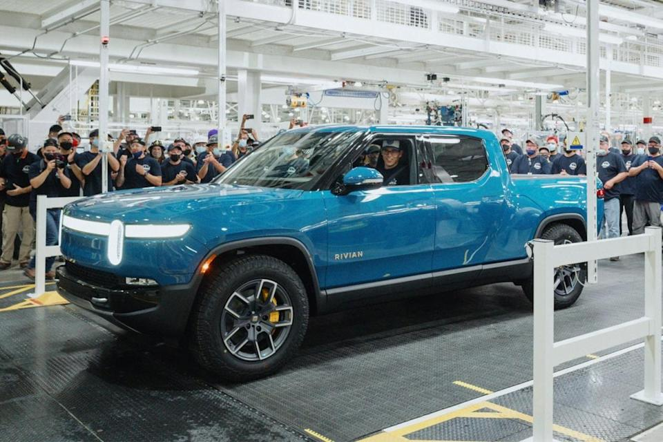 Rivian founder and CEO R.J. Scaringe sitting in a blue electric pickup truck, called the R1T, the first produced in the EV factory in September 2021