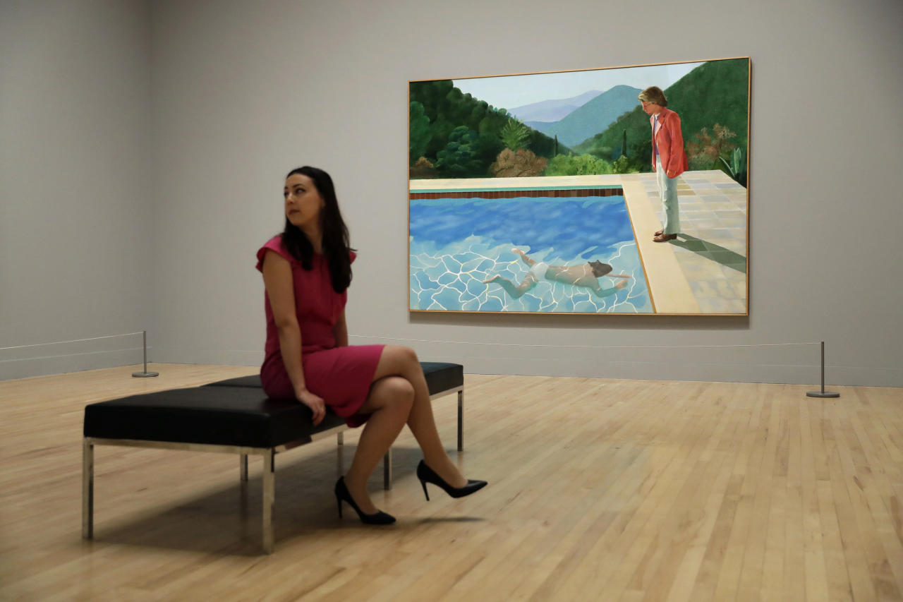 "FILE - In this Feb. 6, 2017, file photo, a Tate representative poses for photographs next to British artist David Hockney's ""Portrait of an Artist (Pool with Two Figures) during a photo call to promote the largest-ever retrospective of his work at Tate Britain gallery in London. The painting, considered one of Hockney's premier works, was sold at auction by Christie's in New York for $90.3 million. (AP Photo/Matt Dunham, File)"