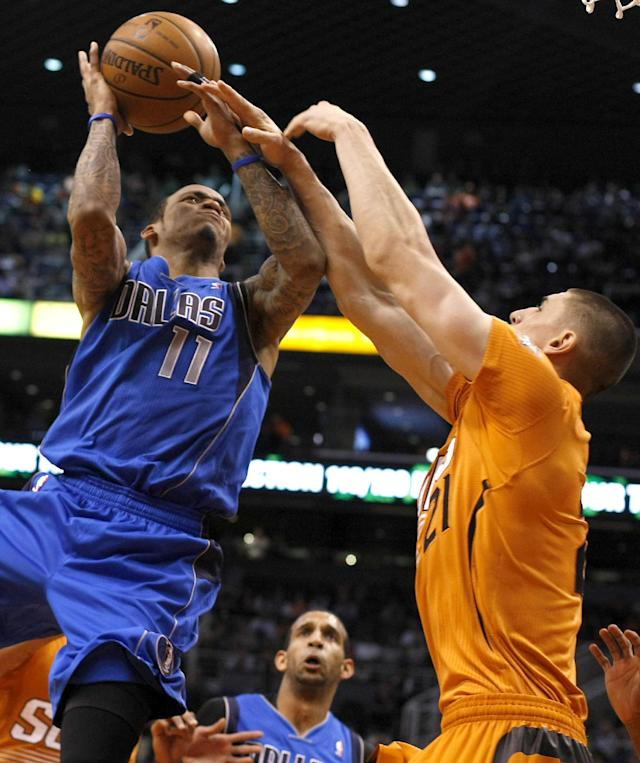 Dallas Mavericks shooting guard Monta Ellis (11) is fouled by Phoenix Suns center Alex Len (21) in the first quarter during an NBA basketball game on Friday, Jan. 17, 2014, in Phoenix. (AP Photo/Rick Scuteri)