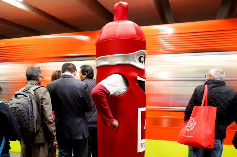 A man wearing a costume, representing a condom, is seen at a metro station, on the International Condoms Day, celebrated a day before Valentine Day, in Mexico City