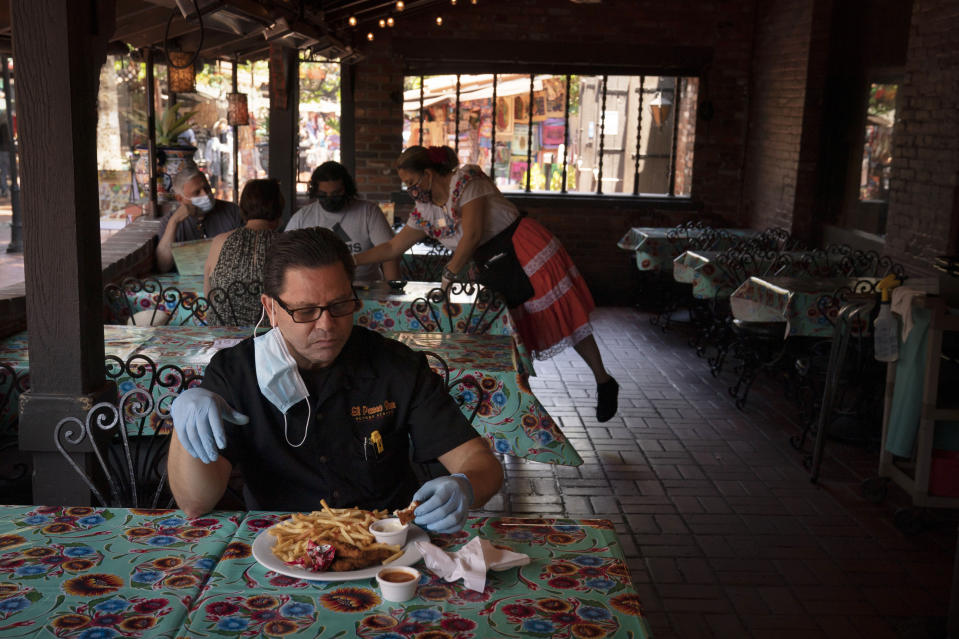 Everardo Gallegos, one of managers at El Paseo Inn Mexican restaurant on Olvera Street, eats his lunch at the restaurant with his protective gloves on in Los Angeles, Friday, June 4, 2021. Olvera Street has long been a thriving tourist destination and a symbol of the state's early ties to Mexico. The location of where settlers established a farming community in 1781 as El Pueblo de Los Angeles, its historic buildings were restored and rebuilt as a traditional Mexican marketplace in 1930s. As Latinos in California have experienced disproportionately worse outcomes from COVID-19, so too has Olvera Street. (AP Photo/Jae C. Hong)