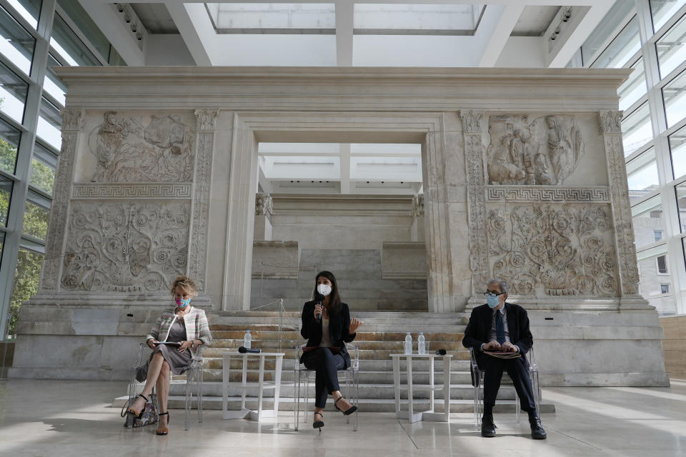 Rome's Mayor Virginia Raggi, center, backdropped by the Ara Pacis (Altar of Peace) presents to journalists an archeological finding emerged during the excavations at a Mausoleum in Rome, Friday, July 16, 2021. The monumental pomerial stone is dating back to Roman Emperor Claudio and was used to mark the 'pomerium' the sacred boundaries of the 'Urbe', the city of Rome, during the Roman empire. (AP Photo/Domenico Stinellis)