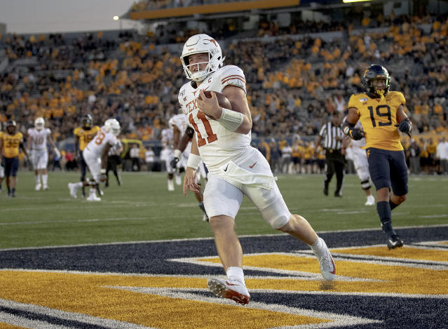 Texas quarterback Sam Ehlinger (11) smiles after scoring a touchdown against West Virginia during an NCAA college football game on Saturday, Oct. 5, 2019, in Morgantown, W. Va. (Nick Wagner/Austin American-Statesman via AP)