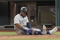 Seattle Mariners baserunner Kyle Lewis sits at home plate after being tagged out to end a baseball game in the ninth inning against the Texas Rangers, Saturday, May 8, 2021, in Arlington, Texas. (AP Photo/Louis DeLuca)