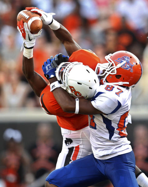 Oklahoma State safety Ashton Lampkin, left, intercepts a pass intended for Savannah State wide receiver Marcus Johnson (87) in the first quarter of an NCAA college football game in Stillwater, Okla., Saturday, Sept. 1, 2012. (AP Photo/Sue Ogrocki)