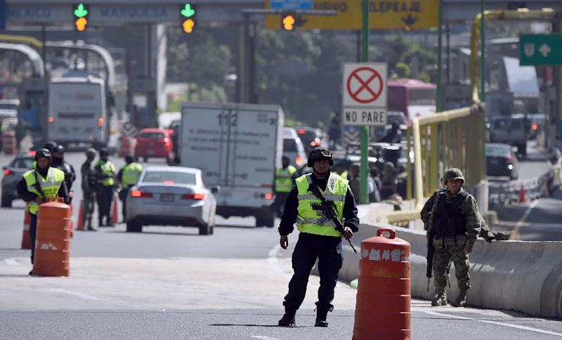 """Federal police and soldiers are seen at a checkpoint in Mexico City, on July 13, 2015 during the hunt for escaped drug kingpin Joaquin """"El Chapo"""" Guzman (AFP Photo/Alfredo Estrella)"""