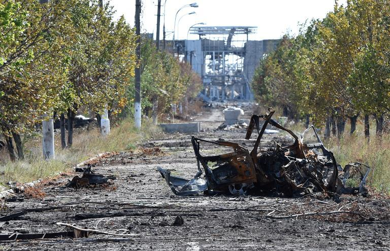 A destroyed vehicle lies on a road leading to the remains of Lugansk International Airport, eastern Ukraine, September 11, 2014
