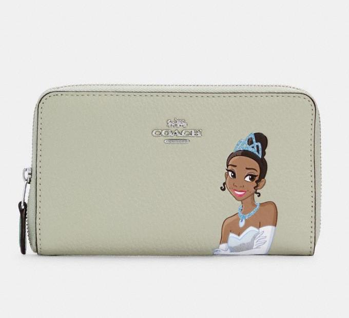 Disney X Coach Medium Id Zip Wallet With Tiana. Image via Coach Outlet.