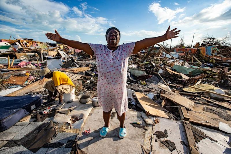 Aliana Alexis of Haiti stands on the concrete slab of what is left of her home after destruction from Hurricane Dorian in an area called