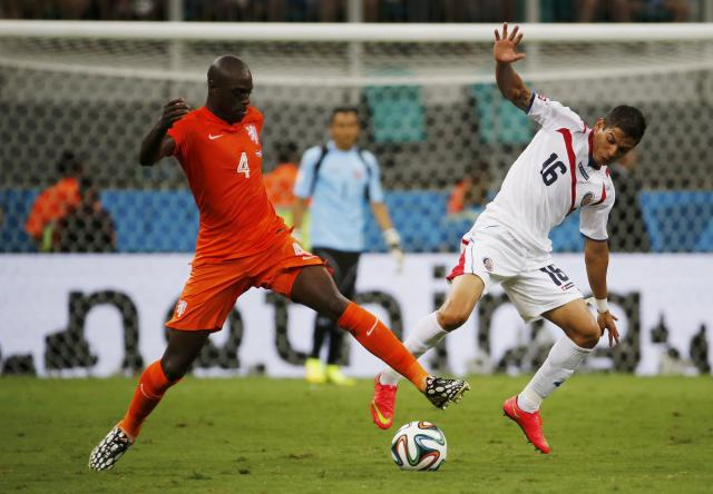 Costa Rica's Cristian Gamboa (R) fights for the ball with Bruno Martins Indi of the Netherlands during their 2014 World Cup quarter-finals at the Fonte Nova arena in Salvador July 5, 2014. REUTERS/Sergio Moraes (BRAZIL - Tags: SOCCER SPORT WORLD CUP)