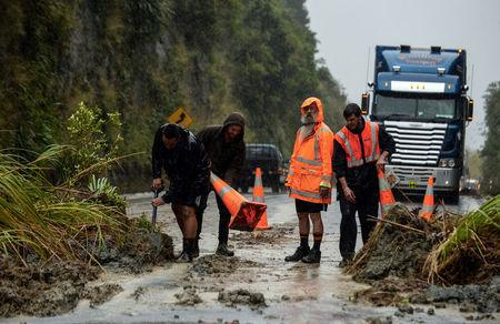 A landslide caused by rains from Cyclone Debbie is shoveled off a main road between Napier and Taupo in New Zealand