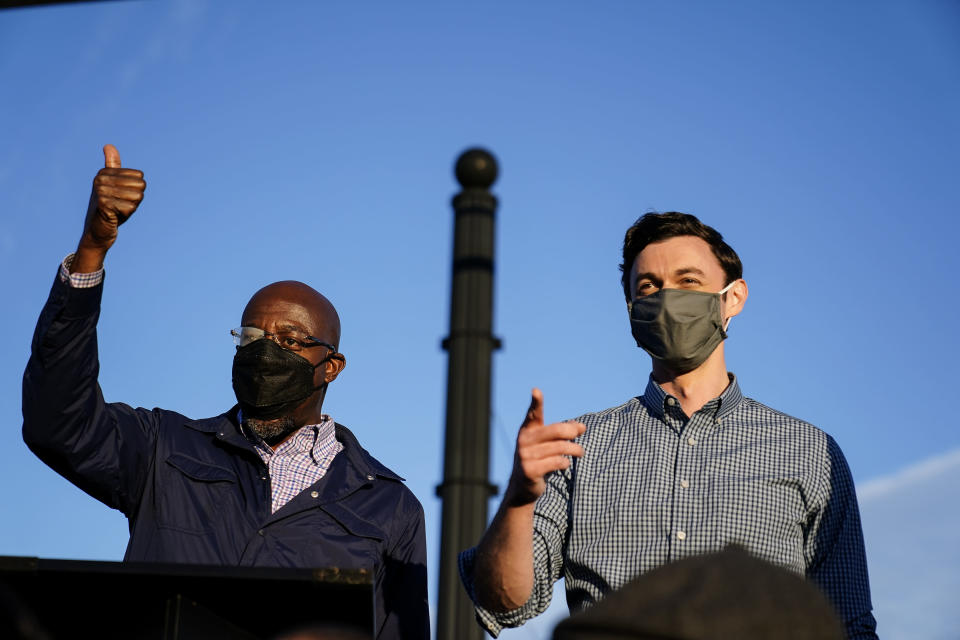 Georgia Democratic candidates for U.S. Senate Raphael Warnock, left, and Jon Ossoff, right, gesture toward a crowd during a campaign rally on Sunday, Nov. 15, 2020, in Marietta, Ga. (AP Photo/Brynn Anderson)