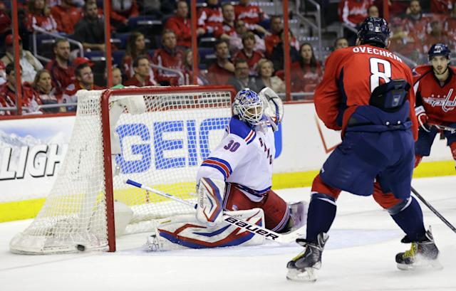New York Rangers goalie Henrik Lundqvist (30), from Sweden, deflects a shot as Washington Capitals left wing Alex Ovechkin (8), from Russia, skates nearby, in the third period, of Game 7 first-round NHL Stanley Cup playoff hockey series, Monday, May 13, 2013 in Washington. The Rangers won 5-0. (AP Photo/Alex Brandon)
