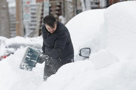 Danny Luis shovels snow around his car as a late winter storm that dumped more than two feet (60 cm) of snow, in Montreal