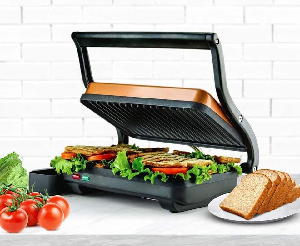 """Get ready to<i>only</i>have ham and cheese sandwiches with crispy, golden brown ridges and gooey, thoroughly heated ingredients.<br /><br /><strong>Promising review:</strong>""""It is quite compact but can easily do two panini sandwiches. Easy to clean. Cooks the paninis nicely. No temperature control, but I don't need it for most sandwiches. Great value for the price!"""" —<a href=""""https://amzn.to/3aiXcsH"""" target=""""_blank"""" rel=""""nofollow noopener noreferrer"""" data-skimlinks-tracking=""""5723569"""" data-vars-affiliate=""""Amazon"""" data-vars-href=""""https://www.amazon.com/gp/customer-reviews/R1M51B15CN3TMB?tag=bfjasmin-20&ascsubtag=5723569%2C3%2C31%2Cmobile_web%2C0%2C0%2C0"""" data-vars-keywords=""""cleaning"""" data-vars-link-id=""""0"""" data-vars-price="""""""" data-vars-retailers=""""Amazon"""">Amazon Customer</a><br /><br /><strong>Get it from Amazon for <a href=""""https://amzn.to/3dpel63"""" target=""""_blank"""" rel=""""noopener noreferrer"""">$28.99+</a> (available in three colors).</strong>"""