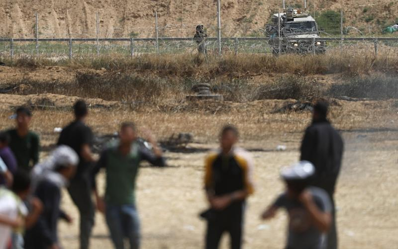 An Israeli soldier aims his weapon as Palestinian protesters gather near the border fence with Israel, east of Khan Yunis in the southern Gaza city on April 13, 2018 (AFP Photo/Thomas COEX)