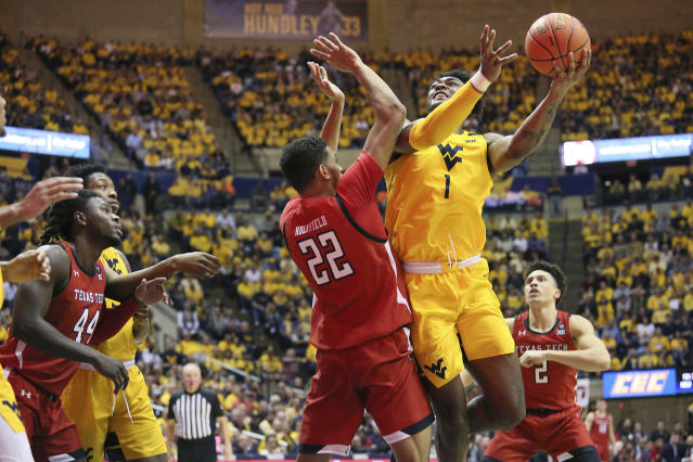West Virginia forward Derek Culver (1) goes to shoot as he is defended by Texas Tech forward TJ Holyfield (22) during the second half of an NCAA college basketball game Saturday, Jan. 11, 2020, in Morgantown, W.Va. (AP Photo/Kathleen Batten)