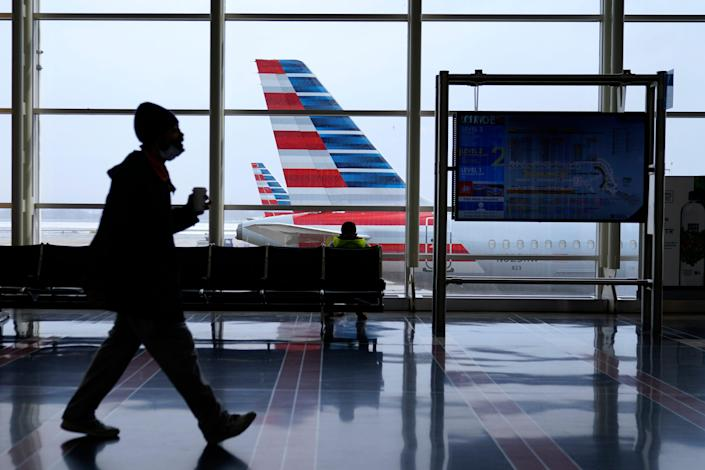 An American Airlines jet sits parked at a gate as light snow falls at Ronald Reagan Washington National Airport, Tuesday, Feb. 2, 2021, in Arlington, Virginia. American Airlines says bookings are coming back. As a result, the airline said it expects to bring back most of its grounded planes by early summer.