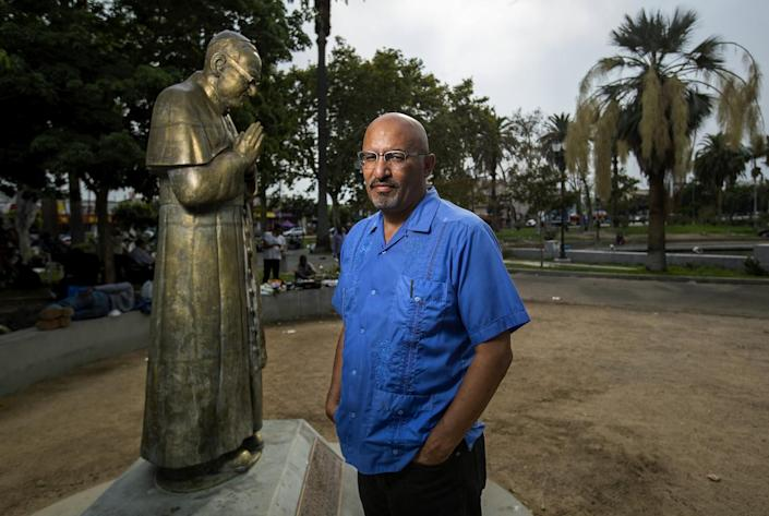 Author Roberto Lovato at MacArthur Park in Los Angeles, next to a statue of St. Oscar Arnulfo Romero.
