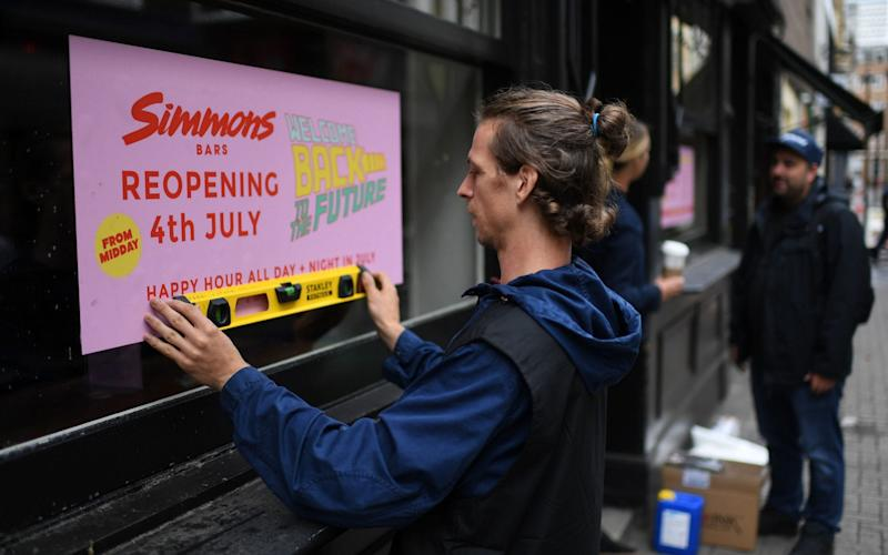 A man works to affix a sign advertising the planned July 4 re-opening of a bar in Soho - DANIEL LEAL-OLIVAS/AFP