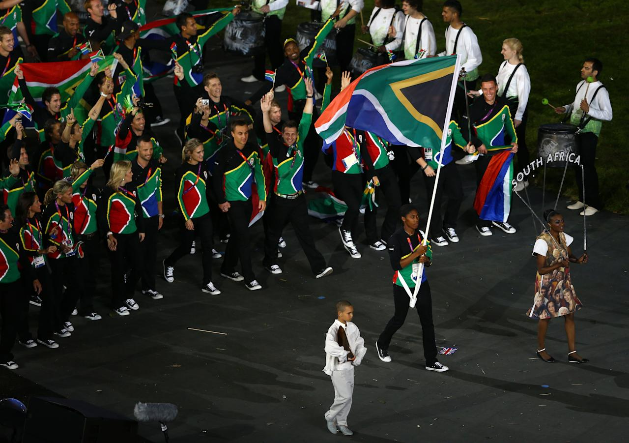 LONDON, ENGLAND - JULY 27: Caster Semenya of the South Africa Olympic athletics team carries her country's flag during the Opening Ceremony of the London 2012 Olympic Games at the Olympic Stadium on July 27, 2012 in London, England.  (Photo by Paul Gilham/Getty Images)