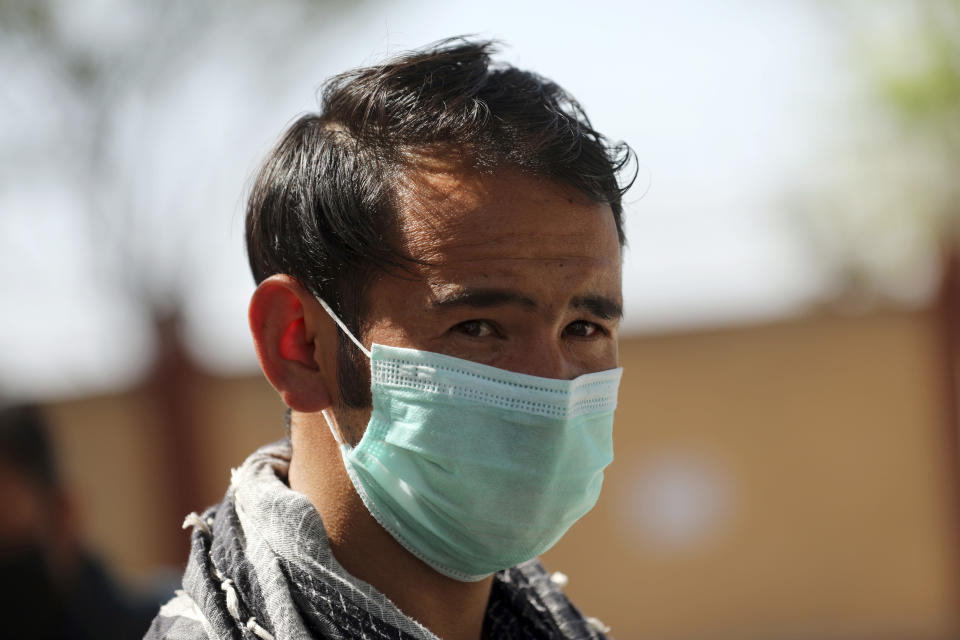 A man wearing a protective face mask to help curb the spread of the coronavirus walks in a street in Kabul, Afghanistan, Sunday, May 30, 2021. (AP Photo/Rahmat Gul)