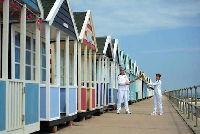 SOUTHWOLD, UNITED KINGDOM - JULY 05: Caroline Emeny and Richard Game carry the Olympic torch past the beach huts on Southwold sea front on July 5, 2012 in Southwold, England. The Olympic Flame is now on day 48 of a 70-day relay involving 8,000 torchbearers covering 8,000 miles. (Photo by Jamie McDonald/Getty Images)