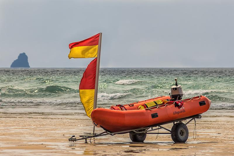 Rigid inflatable boat (Rib) on the beach ready for quick launch by lifeguards watching over the surfers and swimmers in the ocean.