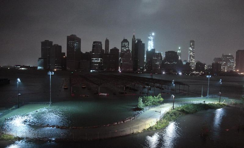 ADDS INFORMATION ON BUILDINGS AND LOCATION - Lower Manhattan goes dark during superstorm Sandy, on Monday, Oct. 29, 2012, as seen from the Brooklyn Heights promenade in the Brooklyn borough of New York. One World Trade Center, background center, remains brightly lit. Sandy continued on its path Monday, as the storm forced the shutdown of mass transit, schools and financial markets, sending coastal residents fleeing, and threatening a dangerous mix of high winds and soaking rain. (AP Photo/Bebeto Matthews)
