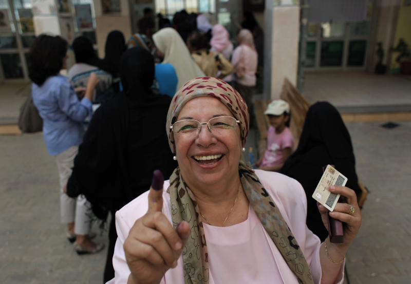 An Egyptian woman shows her ink-stained finger after voting, while others line up in front of their polling station during the first day of the presidential runoff, in Cairo, Egypt, Saturday, June 16, 2012. Egyptians voted Saturday in the country's landmark presidential runoff, choosing between Hosni Mubarak's ex-prime minister and an Islamist candidate from the Muslim Brotherhood after a race that has deeply polarized the nation. The two-day balloting will produce Egypt's first president since a popular uprising last year ousted Mubarak, who is now serving a life sentence. (AP Photo/Nasser Nasser)