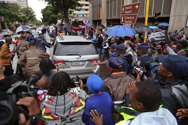 People run after the car that is transporting Oscar Pistorius from the high court after the first day of his trial in Pretoria, South Africa, Monday, March 3, 2014. Pistorius is charged with murder with premeditation in the shooting death of girlfriend Reeva Steenkamp in the pre-dawn hours of Valentine's Day 2013. (AP Photo/Schalk van Zuydam)