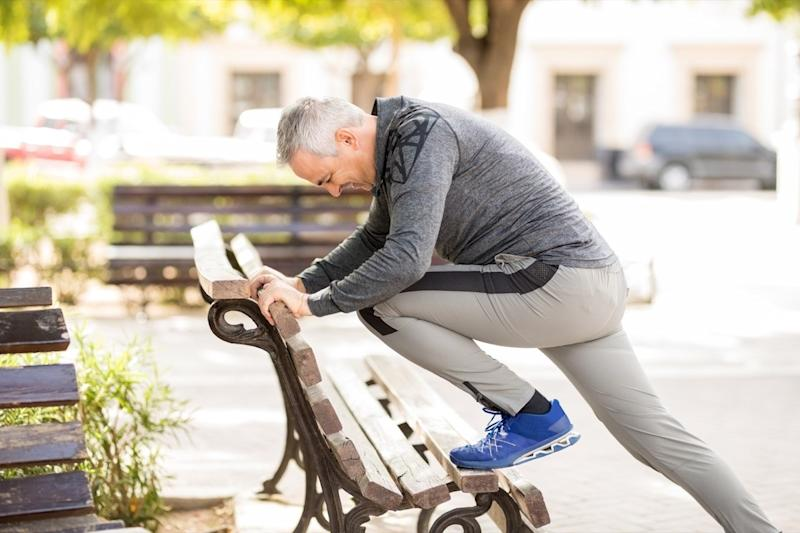 middle aged man stretching on park bench