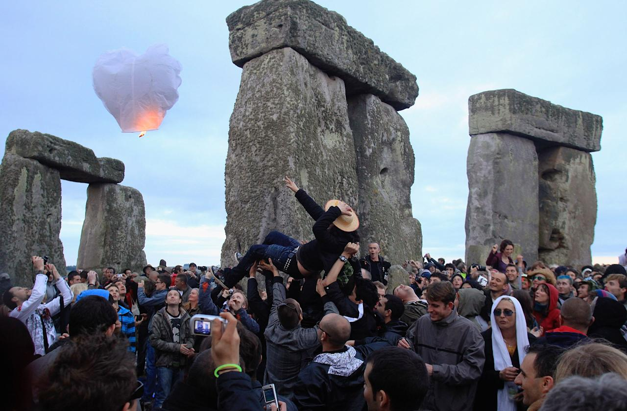 A woman is lifted above the crowd as revellers celebrate the Summer Solstice at Stonehenge on June 21, 2009 near Amesbury, England. Record crowds were expected to watch the sunrise over the ancient monument on the longest day of the year at 4.58am. Cloudy skies meant that the sun was not seen, but the event stayed dry unlike last year. Police had warned they would crack down on anti-social behaviour, treating the event as they would a Saturday night in a city centre. (Photo by Matt Cardy/Getty Images)