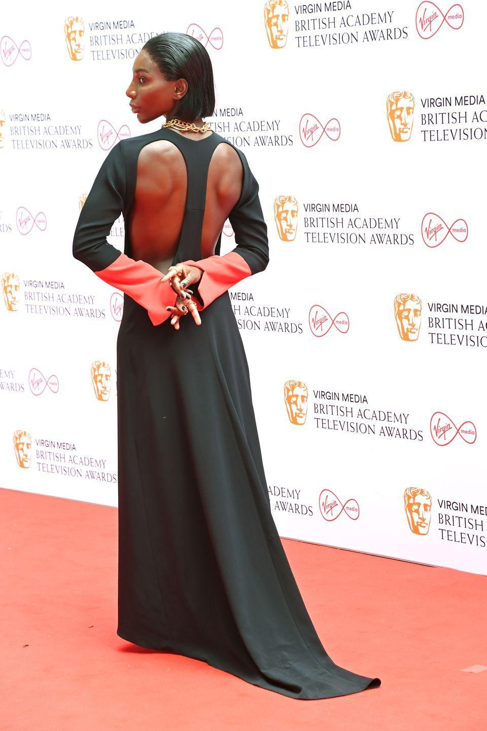 <p>Michaela Coel won big at the awards ceremony, and also wore one of her best red-carpet looks to date, choosing some of the most exciting newgen designers for the big moment. The star shone in a black gown with red sleeves and striking backless detail, which was designed by Maximilian Davis, and accessorised with chunky gold jewellery by Alighieri.</p>